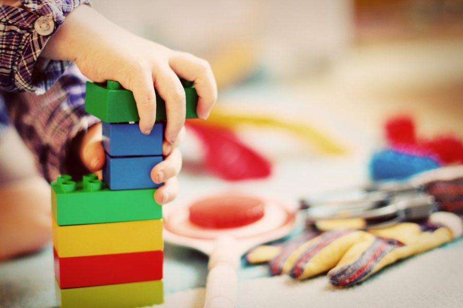 Kinderhände bauen Turm aus Bauklötzen