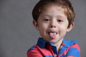Ein kleines Kind streckt die Zunge raus, Sprache als Instrument