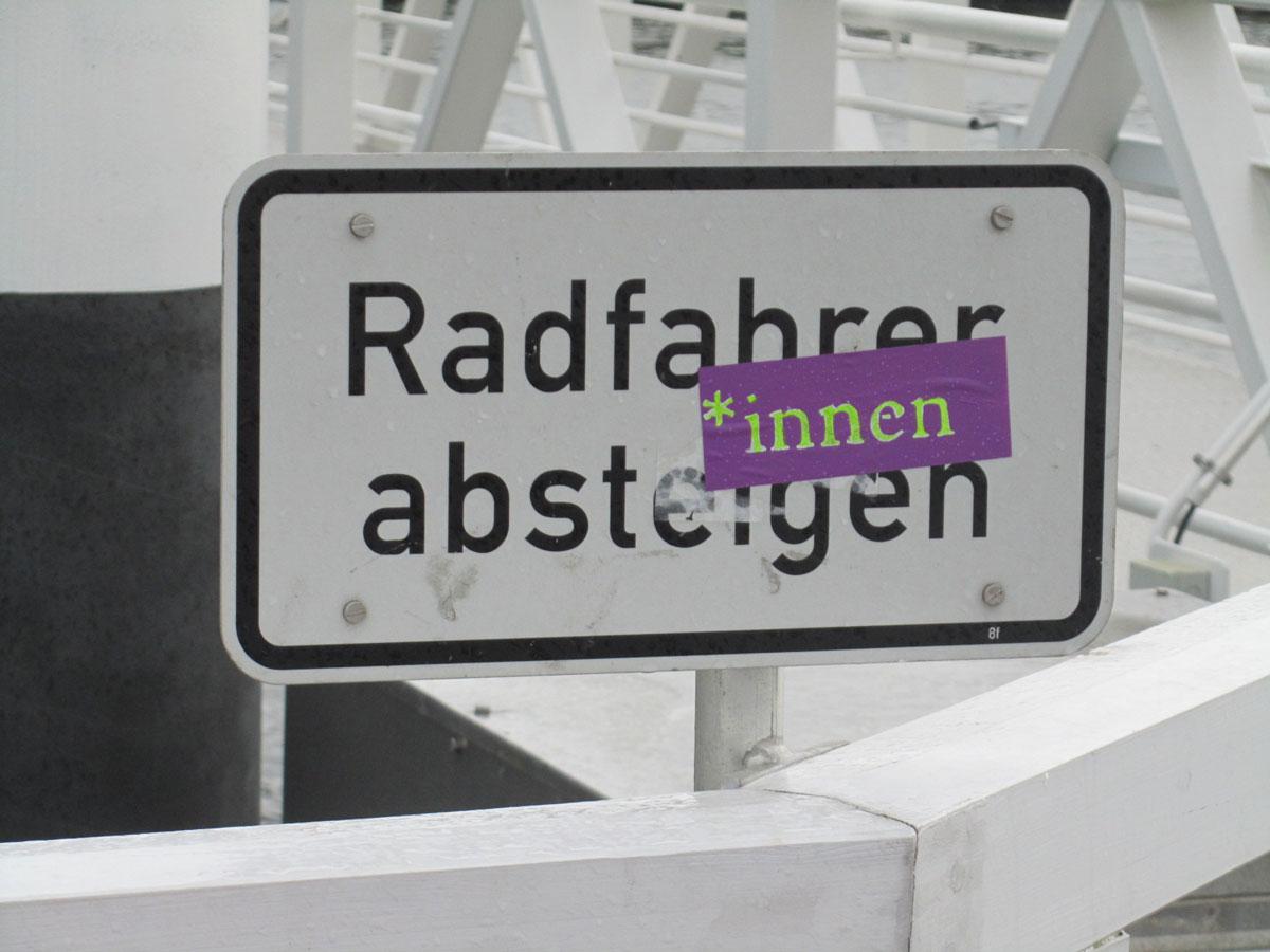 Radfahrer*innen absteigen: Aufkleber an einem Hinweisschild in Kiel (Hörnbrücke)