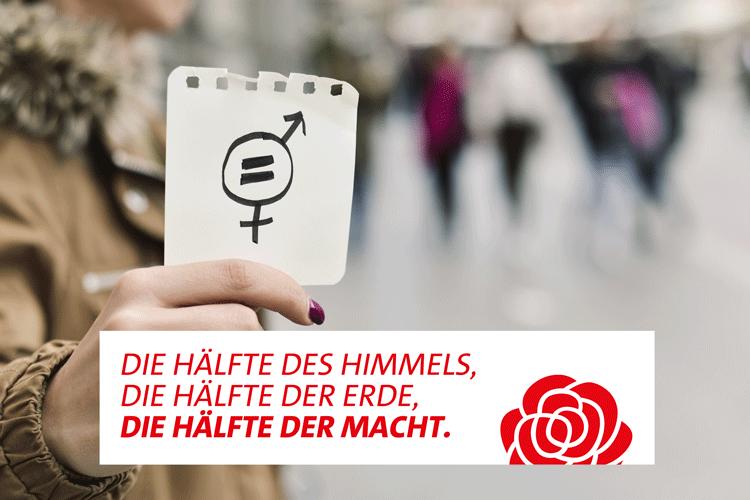 Geschlechtergleichheit als Forderung zum Internationalen Frauentag, eine Frau hält einen Zettel mit einem kombinierten Symbol für Männer und Frauen in der Hand