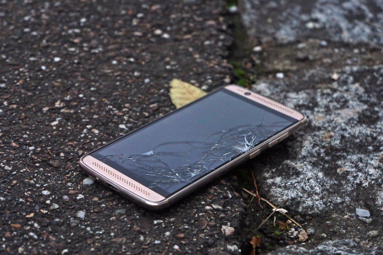 Smartphone mit zerbrochenem Display auf gebrochenem Asphalt