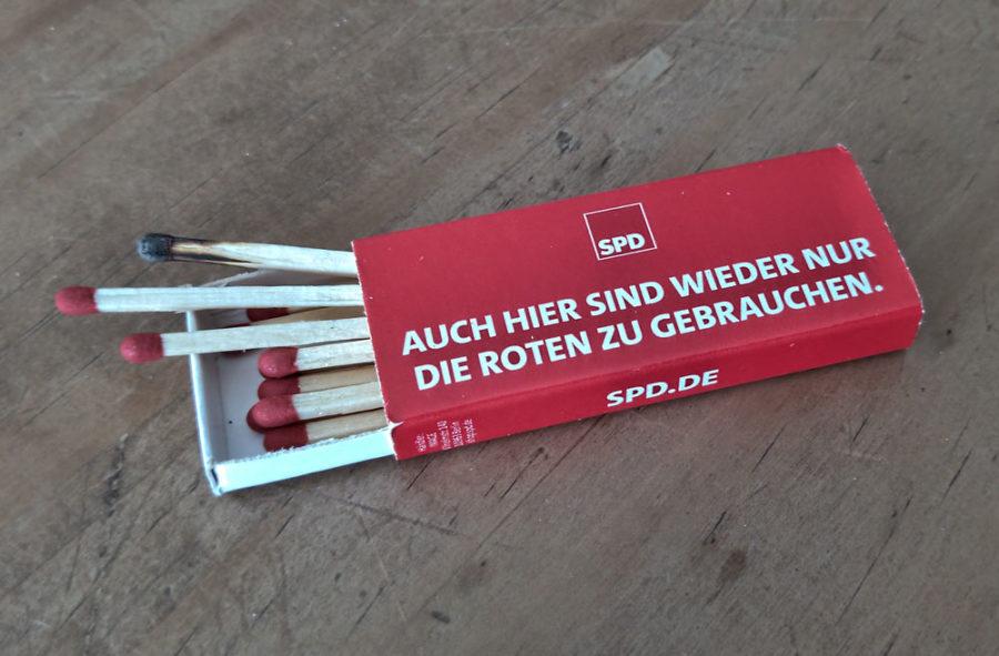 """Streichholzschachtel mit neuen und einem abgebrannten Streichholz und dem Spruch: """"Auch hier sind wieder nur die Roten zu gebrauchen."""""""